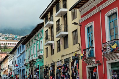 Street in downtown Quito with cloud covered mountains in the background