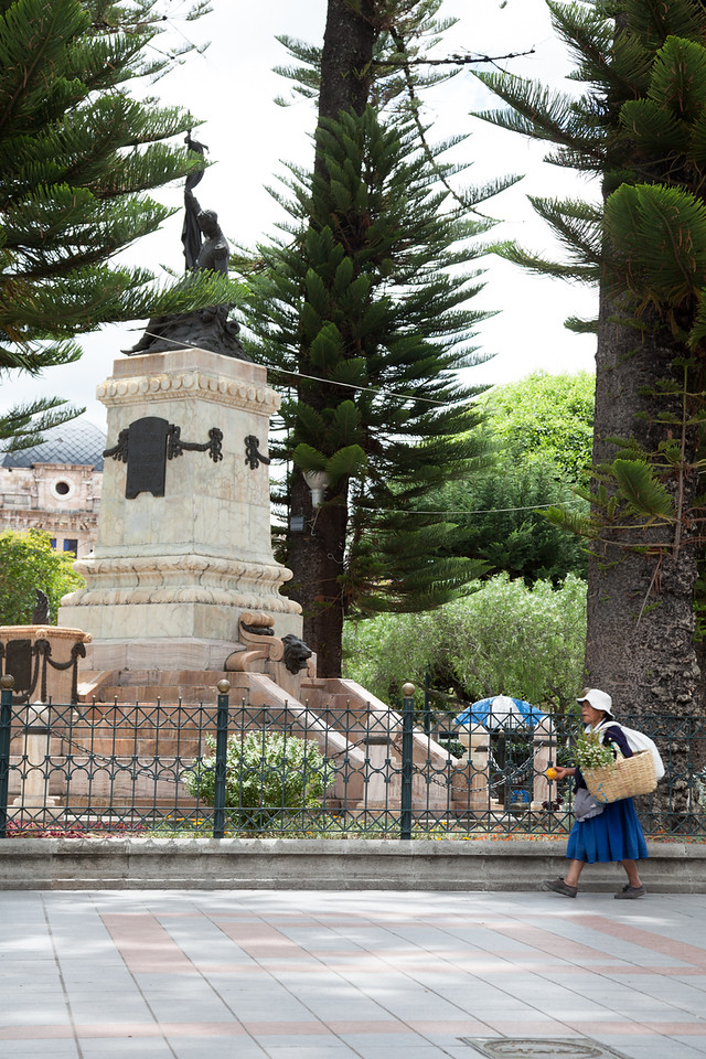 A traditionally dressed woman strolls through Calderón park in front of his statue.