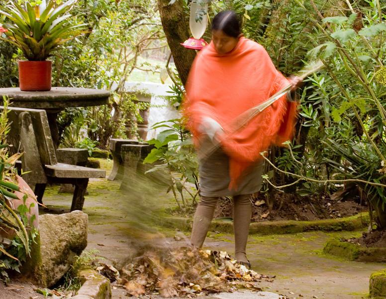 Ecuadorian woman sweeping the garden