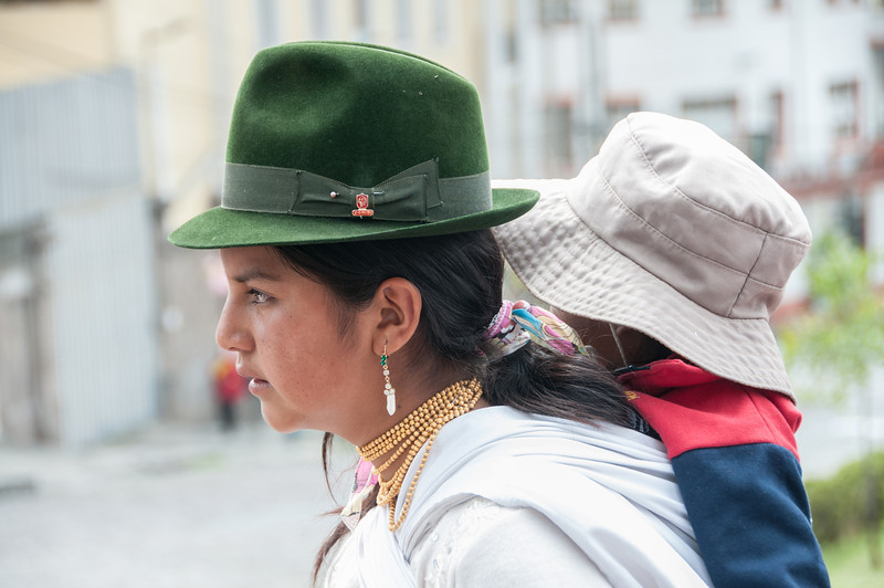• Location - Quito, Ecuador<br /> • A lady carrying her child on her back while trying to hawk some of her goods
