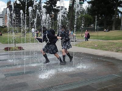On the edge of La Carolina Park school girls run through a water art works.