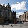 Sobre la izquierda se ve la Catedral de St Giles. Aunque fue fundada en 1130, su rol central en la vida de Edimburgo fue sujeto mas a cambios que otras iglesias y como resultado de eso la mayor parte del exterior fue remodelada en 1833 y el interior que se ve hoy fue producto de la remodelacion de 1883. Mas alla de su nombre St Giles Cathedral, no es una catedral. El titulo da una idea de su magnifica escala pero fue estrictamente Catedral durante 2 cortos periodos cuando obispos sirvieron en la iglesia desde 1633-8 y desde 1661-89.