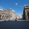 """City Chambers. El edificio fue disenado por John Adam de la famosa familia de arquitectos y costo 31,000 libras entre 1753-1761. Fue construido sobre varios de los """"Closes"""" medievales incluido Mary King's Close. Su intencion original fue como un mercado real  para proveer a Edimburgo de un lugar donde la comunidad comercial pudiera hacer sus negocios, los mercaderes prefirieron las tavernas y la misma High Street para cerrar sus negocios. Fue entonces cuando el cosejo de la ciudad tomo parte del edificio en 1811 y ordeno ampliaciones hacia el ala norte."""