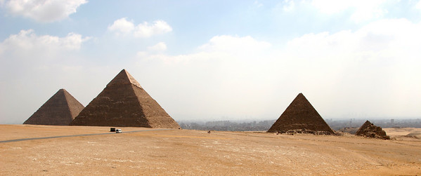 Giza Pyramids - From left, the Great Pyramid of Khufu, Pyramid of Khafre, Pyramid of Menkaure, and smaller remains of Pyramids of the Queens.  The city of Cairo is in the background.