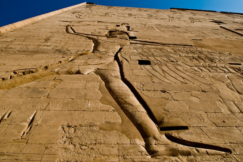 Title: The Long Stride of Pharaoh<br /> Date: October 2009<br /> A huge carving of Horus, in the classic pose of a pharaoh subduing his enemies, at Edfu Temple.  It is carved into one of the giant pylons of the temple's exterior.