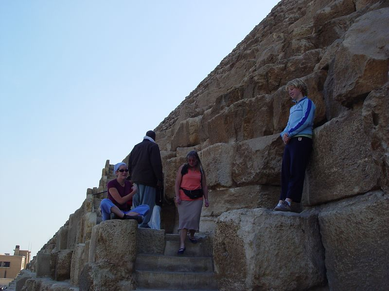 d) We started climbing the great pyramid of Khufu but your not allowed to go above a certain point. Some watchmen is yelling at us to get down. Megan is sitting on the left and Jess is standing on the right.<br /> Later we enter the pyramid of Menkaure. It's not for the people with claustrophobia. The passageways are narrow and steep. It gets pretty hot  and humid the deeper you go.