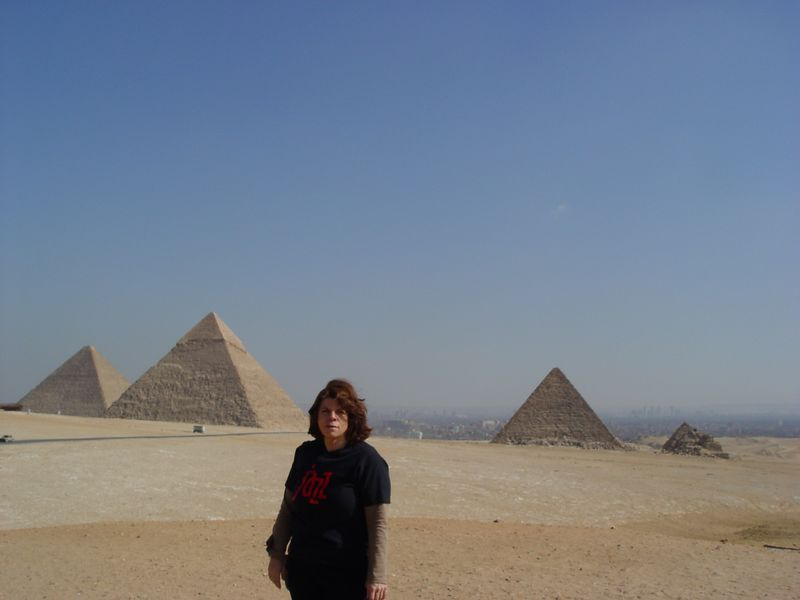 """a) In the morning of the second day in Egypt we travel to the pyramids of Giza. You can see Cairo in the background of Giza plateau. These are the pyramids of Khufu, Khafre and Menkaure. The four sides of the pyramid are accurately oriented to the cardinal points of the compass<br /> I pose in front of the pyramids with my Jazz Semiconductor T-shirt. This photo will be posted on the """"Where's Jazz"""" website. <br /> I already had two other photos posted on the Jazznet, one for Belize and one for skydiving."""
