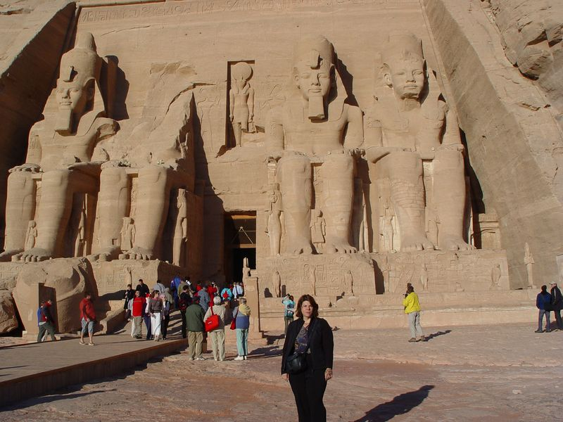 b) Here I am posing in front of the  Great Temple. This temple was built by Ramesses II around 1270 B.C. in ancient Nubia to demonstrate his power and his divinity. The four statues of him are 65 feet/20 meters high. This temple faces the east, and Re-Horakhty is directly above the entrance. <br />  Ramesses either had a big ego or just a good PR man.