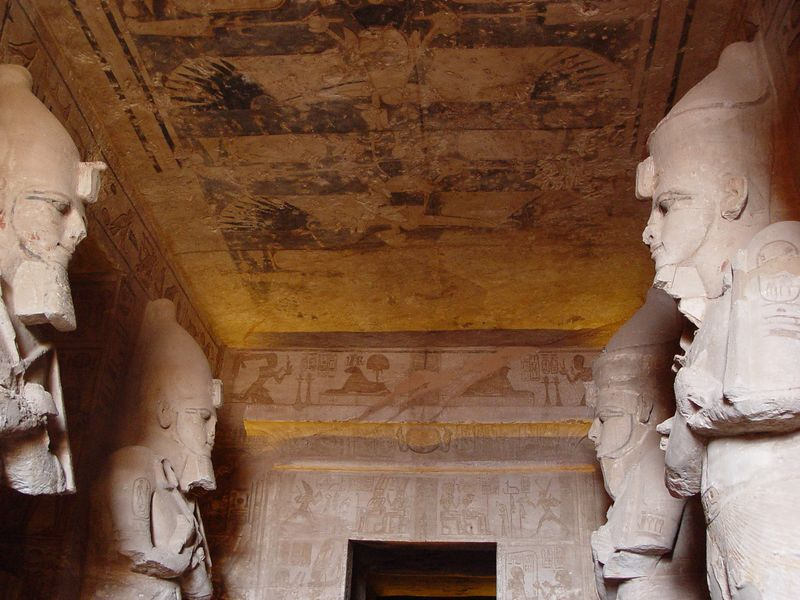 c) The hypostyle  hall within the temple contains eight large statues of the king as Osiris, four on each side, which also serve as pillars to support the roof. The walls are decorated in relief with scenes showing Ramesses in the great battle of Kadesh on the north, and Syrian, Libyan and Nubian wars on the south wall.