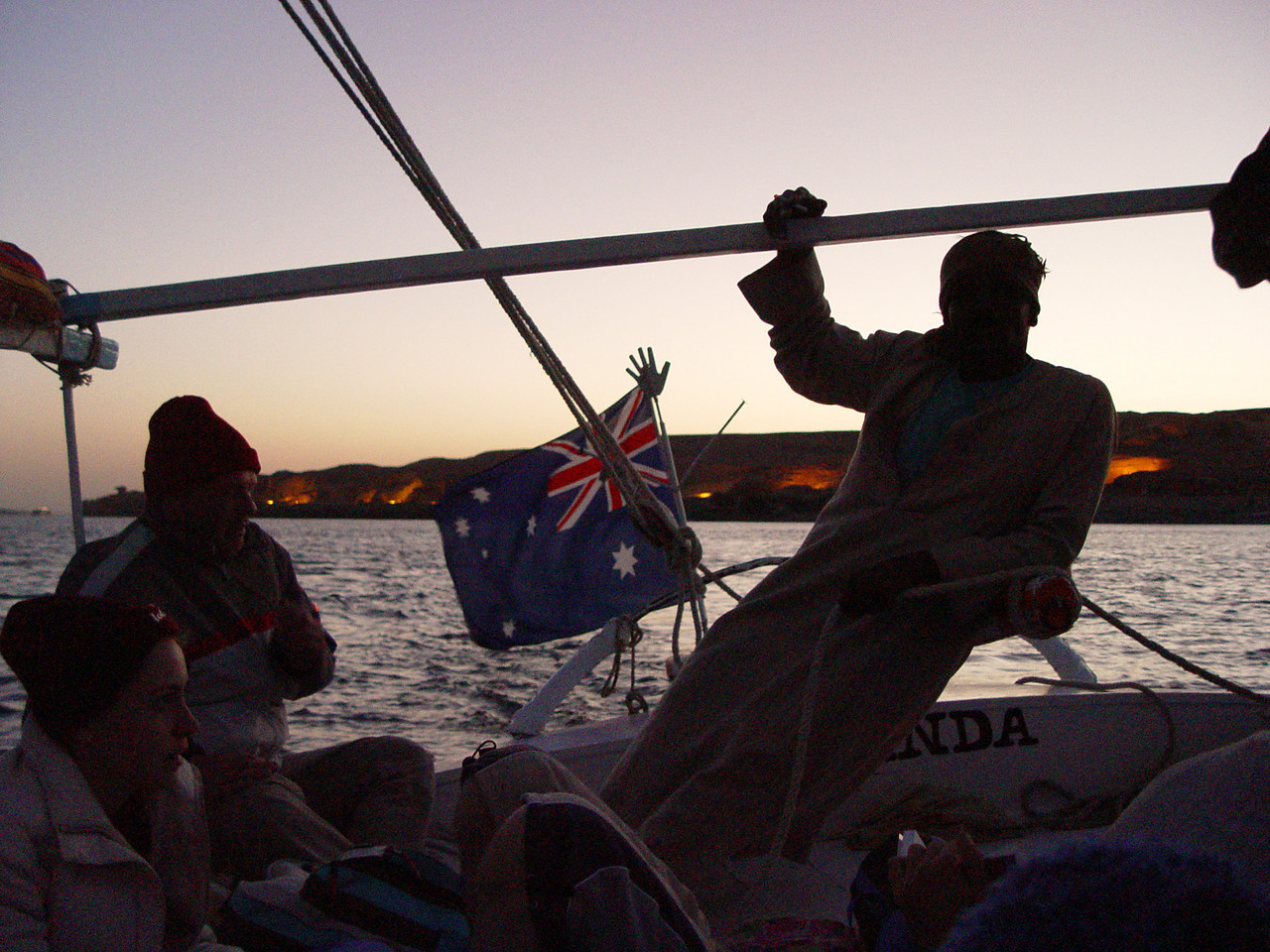 l) Dusk  falls on the felucca.  You can see openings carved into the rock which are lit up.  Lisa comments that it would be great if we could sleep in those openings tonight since it was so cold last night. Everyone says yeah!. However, Tony doesn't think it's such a great idea to sleep with all those mummies. Those are the tombs of Gebel el Silsila.