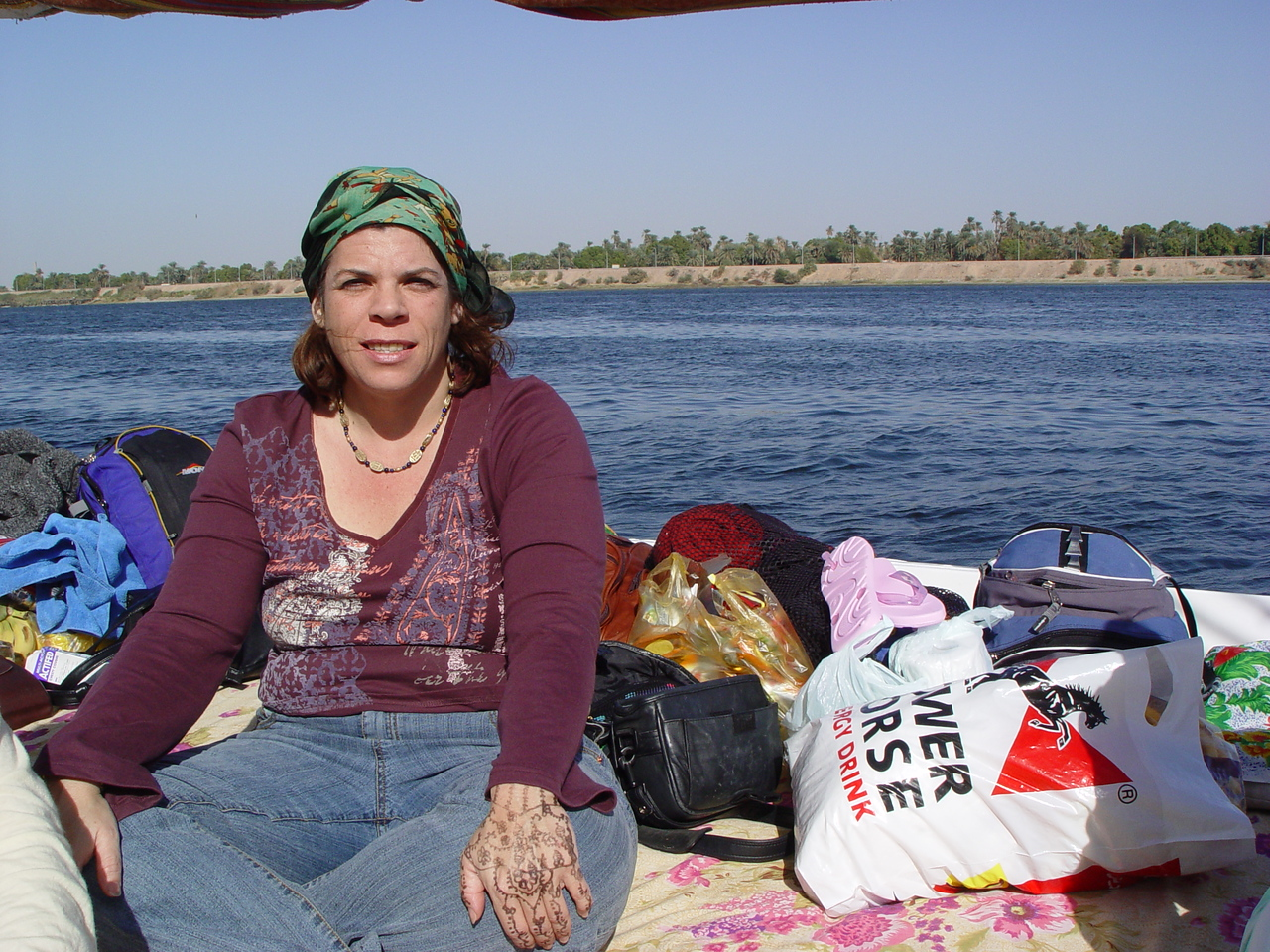"b) Here I am, you can see the henna tattoo on my left hand from Sehel, the nubian island village. The felucca cruise is interesting in that we are sailing downstream with the current but against the wind. So we have to tack the sail which means traversing the nile from side to side to work our way to Luxor. This becomes a tactical problem when you have to avoid hitting the occasional larger cruise ship passing by. There is one point where there is this bridge where we have to lower the mast to avoid hitting the bridge. The crew gets a little frantic in their operation. Tony tells us that one felucca actually had the mast snap in half on the last tour. Brett refers to this as ""the bridge of death"""
