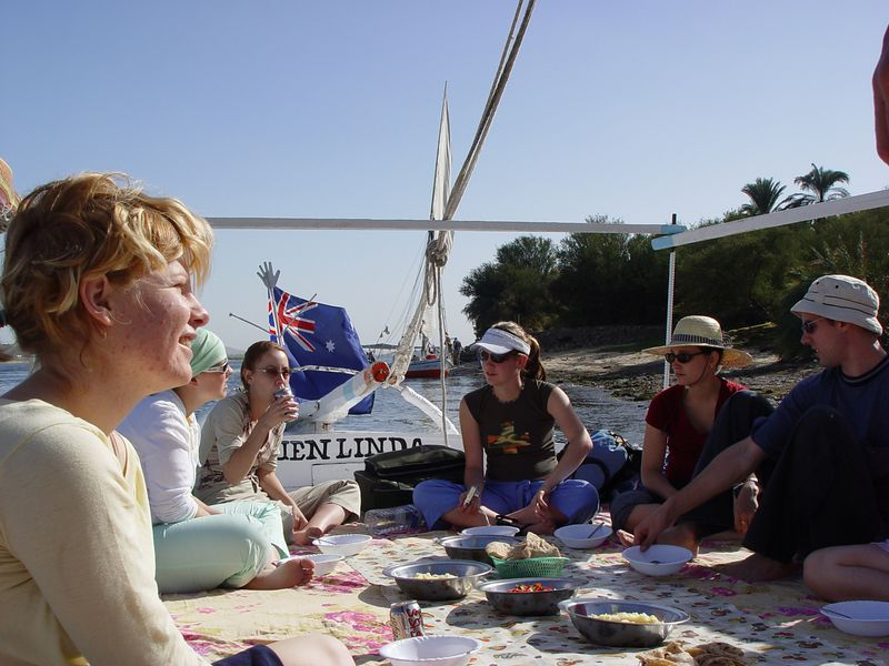 a) Day 1 of the felucca cruise. In the photo from left to right are Jess, Lisa, Jenna, Megan, Alexis, and Brett, Tracey's knee, not in the photo is Scott next to Tracey, Me next to Jess and Tony behind me. You can see we are flying the Australian flag, there is an egyptian flag up front, no American flag, I'm out numbered. The boat's name is Quen Linda. We are having a simple lunch consisting of nubian bread (oh noooo! this was the beginning of our eventual distate for bread, bread and more bread), mixed veggies in tomato sauce, rice and macaroni. We would get some meat for dinner such as lamb, kofta, or chicken. Our breakfasts consist of more bread, jam, and water buffalo cheese.