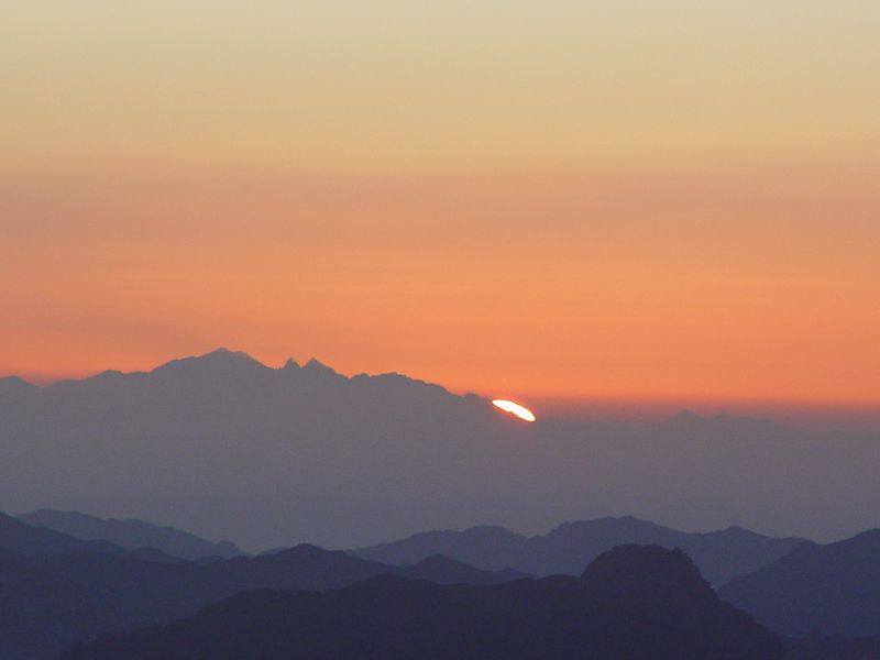e) First sun peaking over the mountain. There is a japanese group which start to sing.