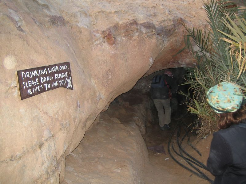 t1) Tony points out a source of fresh water. There is a small cave we wander into and I actually drink the water from the pool in the cave. It was refreshing and no I did not get sick