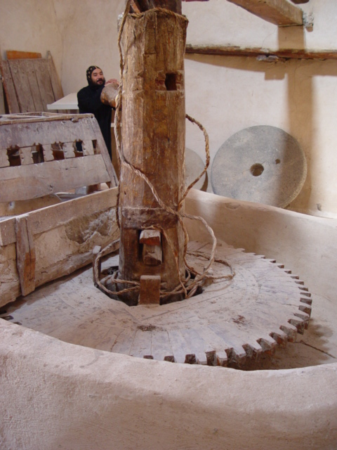 f) The monk shows us a old mill used fro making bread.