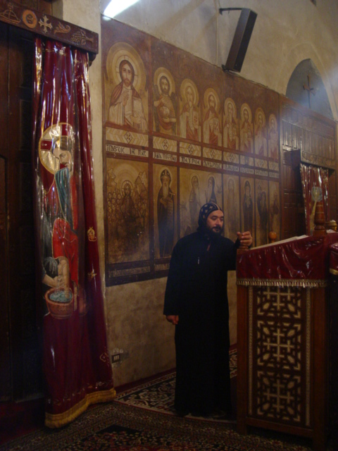 b) The only english speaking monk gives us a tour.<br /> This Coptic monastery is named after Bishoi, who died in 417. His body is still in the monastery, and the monks claim it remains uncorrupted in the casket.