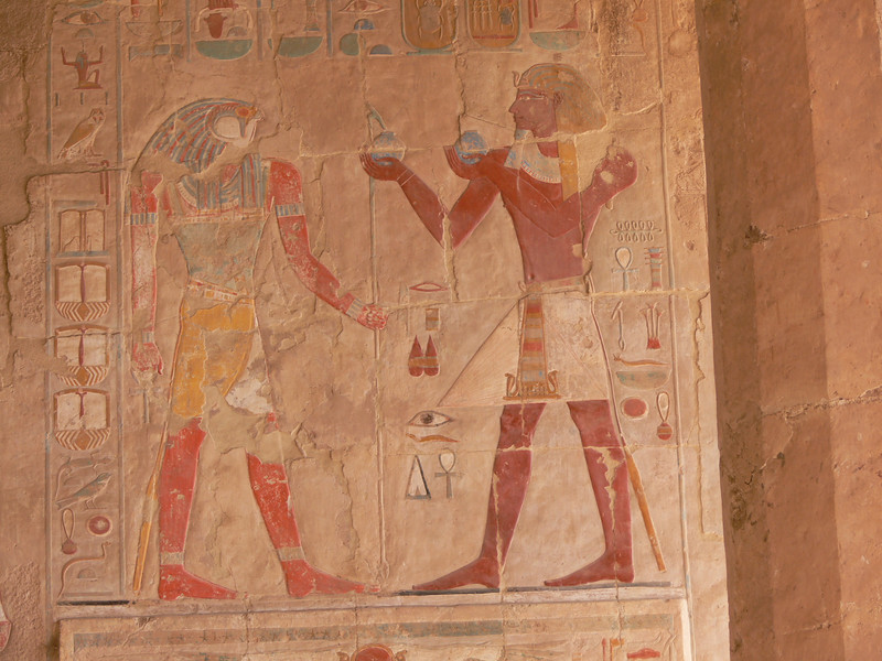 In the Chapel of Anubis, a scene of Queen Hatshepsut, depicted with male features, in the act of ritual offering of wine to Re-Harakhty.