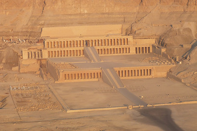 """The mortuary temple of Hatshepsut (c.1478/72-1458 B.C.E.) dates from the New Kingdom. It nestles at the foot of the cliffs in a natural """"bay"""" on the West Bank of Luxor. This area had long been sacred to the goddess Hathor and was the site of the earlier mortuary temple and tomb of King Nebhepetre Mentuhotep (c.2008-1957 B.C.E.) of the Middle Kingdom (ramp visible on the far left). After the introduction of Christianity, Hatshepsut's temple was used as a monastery, hence its modern name, Deir el-Bahri, Arabic for """"Northern Monastery."""""""
