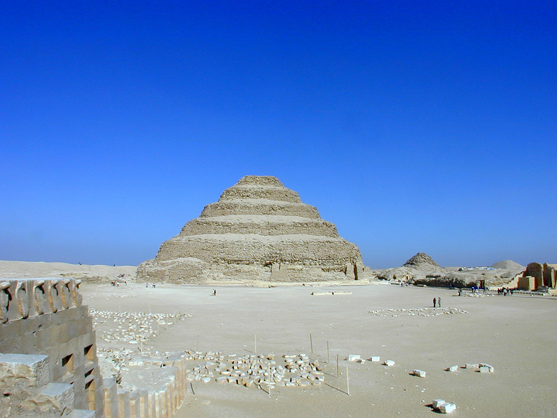 View of the forecourt of the Step Pyramid of Djoser at Saqqara, with a section of the Uraeus-topped perimeter wall at left. The rubble mound immediately to the right of the Step Pyramid is the Pyramid of Userkaf. The third mound, at the right of the picture is the Pyramid of Teti.