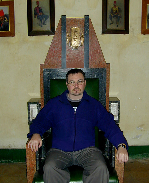 Your intrepid photographer slouches exhaustedly on the wonderful Art Deco bi-coloured granite throne of Farouk, Egypt's last king, in a dusty, forgotten corner of the Manial Palace, Cairo.