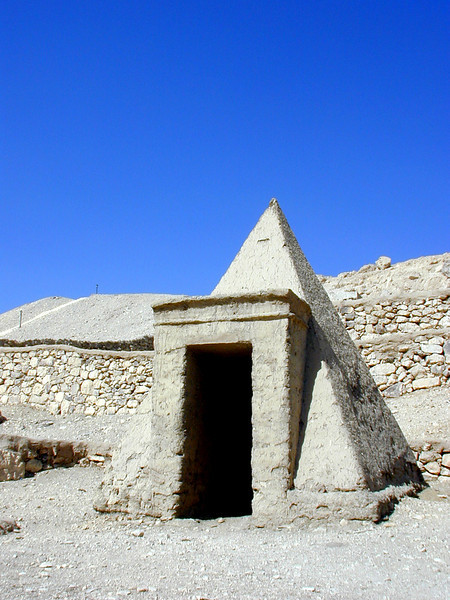 Small pyramid tomb at Deir el Medina. This ancient town was the home to the artisans and builders who constructed the New Kingdom pharaoh's tombs in the nearby Valley of the Kings. In their spare time they built their own elaborate tombs, of which this is one example; the burial chamber is buried deep underground, with access via a tunnel below the pyramid.