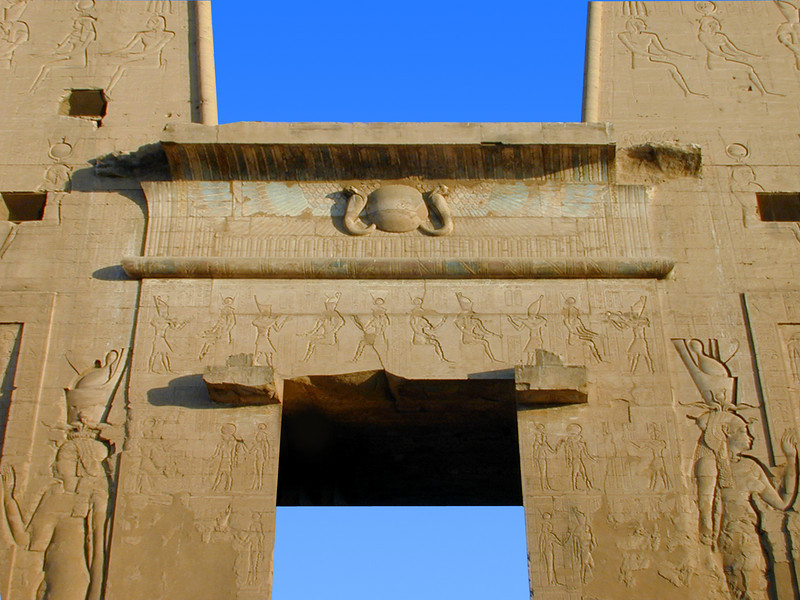 Detail of the main pylon and gateway to the Temple of Horus, Edfu. The female pharaoh depicted on either side of the entrance is Cleopatra VII (of Antony and Cleopatra fame). Note the remnants of red, white and blue paint surrounding the Uraeus at the top of the lintel; originally the entire temple exterior and interior walls would have been brightly painted in these colours.