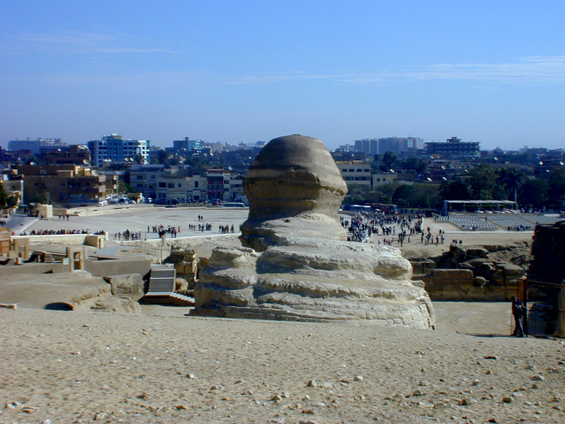 The view of the Sphinx that the travel brochures don't show you; the ageless and inscrutable Sphinx stares across a concrete carpark at a group of suburban Cairo apartment buildings and twenty million tourists from every country on the planet.