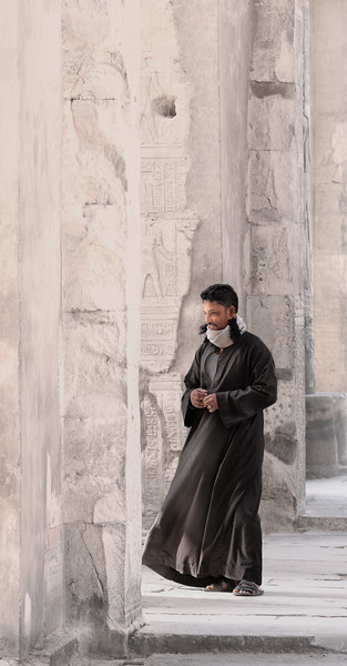 A local Egyptian strolls among the pillars at the KomOmbo Temple