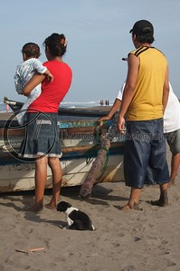 Whew! That was heavy. (funny little dog) The fisherman and his family after bringing in the catch of the day.