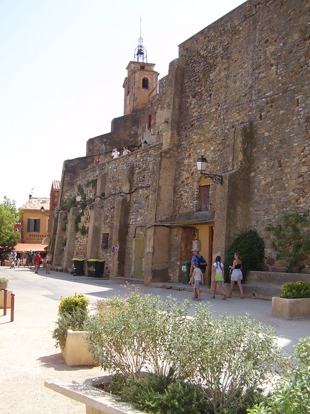 A view of the clock tower with the metal cage bell tower which is characteristic of towns in Provence.