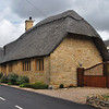 Typical Cotswold home: honey-colored limestone, thatched roof.