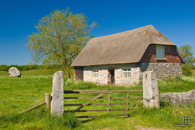 Thatched barn with an Avebury Stone behind