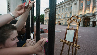 Crowds clamour to take pictures as an easel (R) announcing the birth of Prince William and Catherine, Duchess of Cambridge's baby boy is placed in the forecourt of Buckingham Palace in London on July 22, 2013. Prince William's wife Kate on Monday gave birth to a baby boy who will one day be heir to the British throne, Kensington Palace said in a statement.  AFP PHOTO / WILLOLIVER        (Photo credit should read WILL OLIVER/AFP/Getty Images)