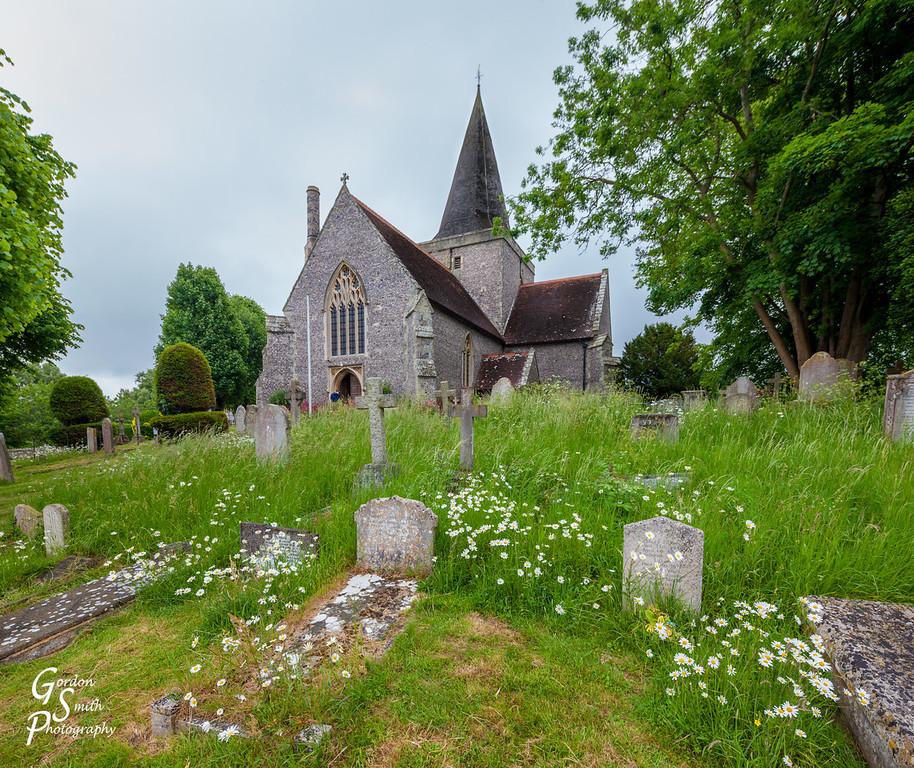 Church and Cemetery with flowers in Alfriston, UK