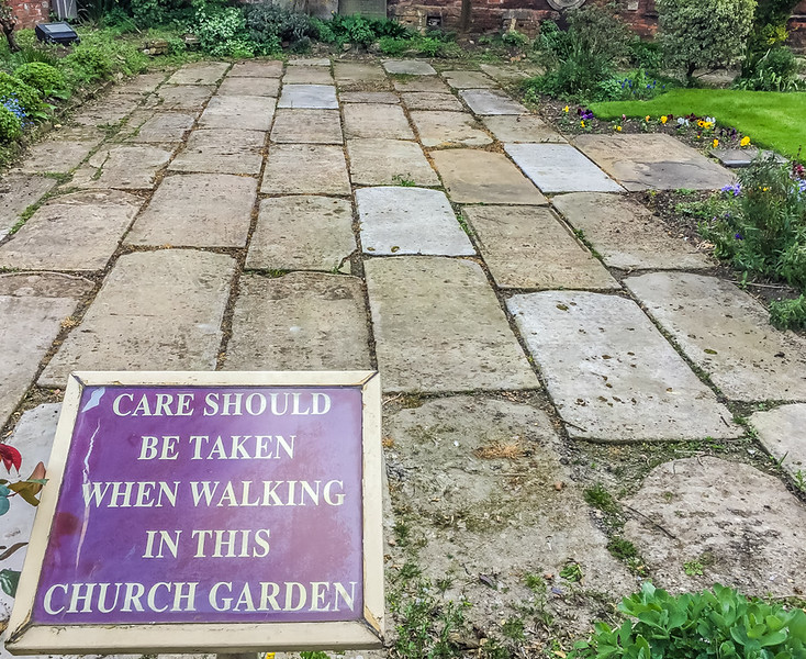 """John Bunyan Museum garden. One reason that """"care should be taken when walking in this church garden"""" is that those slabs of concrete are tombstones laid flat! This grassy area was once the church cemetery, but had been turned into a garden, and the headstones turned into payment."""