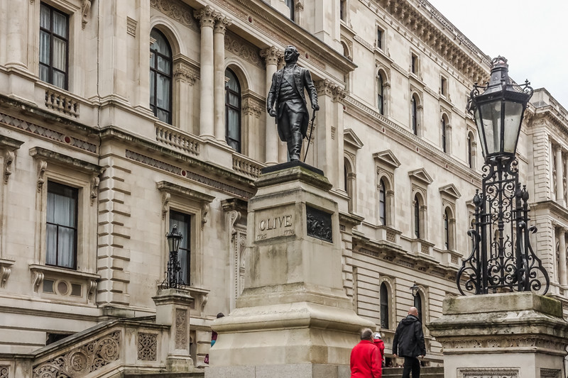 "A view from near the entrance to the <a href=""https://goo.gl/maps/fSyFXy3JGkv"">Churchill War Rooms</a>. A statue of Robert Clive, with the Foreign and Commonwealth Office to the left.<br><br>  Major-General Robert Clive, 1st Baron Clive, KB, FRS (29 September 1725 – 22 November 1774), also known as Clive of India, Commander-in-Chief of British India, was a British officer and soldier of fortune who established the military and political supremacy of the East India Company in Bengal.<br><br> Clive was one of the most controversial figures in all British military history. His achievements included establishing control over much of India, and laying the foundation of the entire British Raj. For that he was vilified by his contemporaries in England, and put on trial before Parliament. Of special concern was that he amassed a personal fortune in India. Modern historians have criticised him for atrocities, for high taxes, and for the forced cultivation of crops which exacerbated famines. (<a href=""https://en.wikipedia.org/wiki/Robert_Clive"">Wikipedia</a>)"
