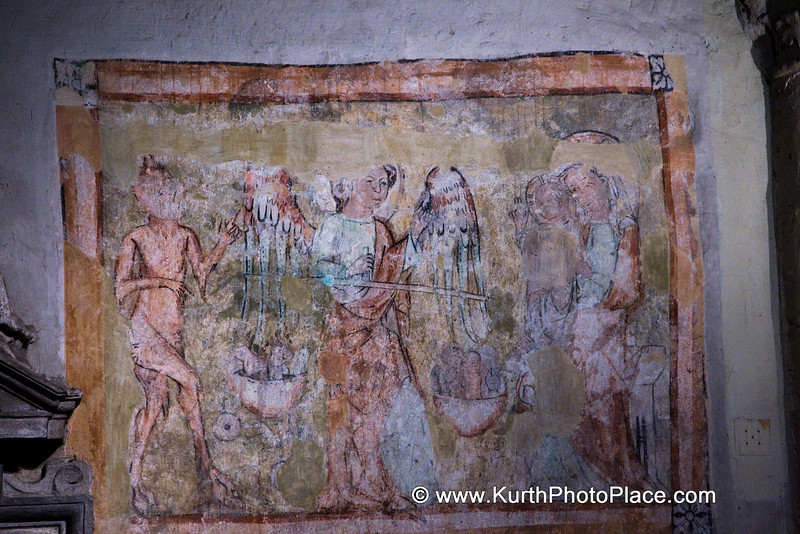 This is a fresco that was discovered in Michael's Church in Vienna.  It is believed to date from the 1400's,  There is an angel in the center - probably  Michael.  The devil is on the left and God is on the right.