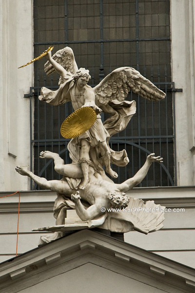 The present façade was built in 1792 in a Neoclassical style by Ernest Koch, a typical style for the reign of emperor Joseph II. Above the entrance, on top of the pediment, resting on Doric columns by Antonio Beduzzi, stands a group with winged angels and St. Michael slaying Lucifer (1725). These sculptural figures were executed by the Italian sculptor Lorenzo Mattielli, who also sculpted the Hercules figures at the Hofburg entrance, just opposite the church.