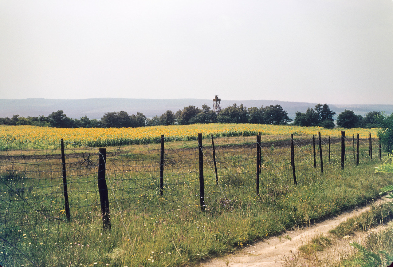 Iron Curtain, plowed ground, barbed wire fences and watch tower, at the Austrian-Hungarian border near Eisenstadt