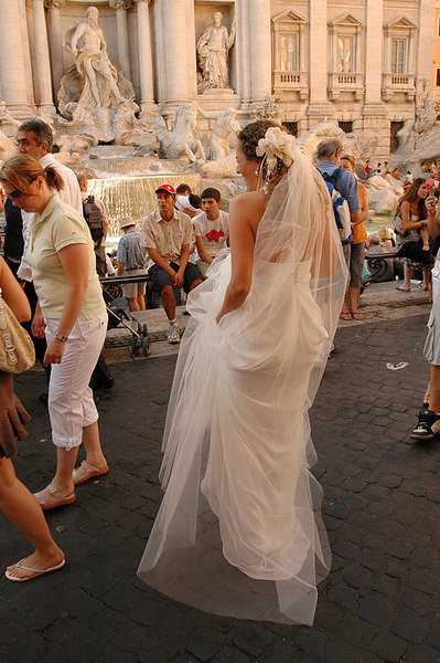Bride posing for photos at the Trevi Fountain.