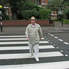 """Walking in the famous Abbey Road crosswalk in London, England.  This crosswalk was made famous by the Beatles """"Abbey Road"""" album cover.  It is still an active crosswalk and a popular tourist attraction for Beatles fans."""