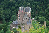 """Burg Eltz - Wikipedia says """"Burg Eltz is a medieval castle nestled in the hills above the Moselle River between Koblenz and Trier, Germany. It is still owned by a branch of the same family that lived there in the 12th century, 33 generations ago. The Rübenach and Rodendorf families' homes in the castle are open to the public, while the Kempenich branch of the family uses the other third of the castle."""""""