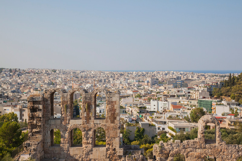 A wide view of Athens with a partial wall from the Odeion of Herodes Atticus in the foreground (built in 161 AD).