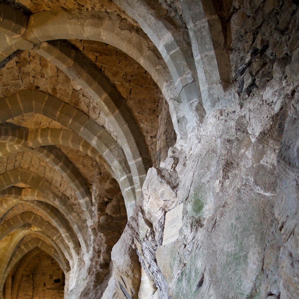 """Bonivard's prison at chateau; """"this prison owes its fame to the English poet Lord Byron, who in 1816 recounted the tale of captivity of Francois Bonivard (1493-1570) in this dungeon in his poem The Prisoner of Chillon"""""""