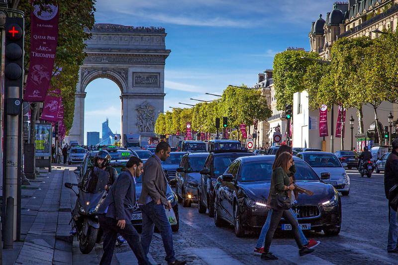 Crossing Champs-Élysées, with the Arc de Triomphe de l'Étoile in the background.