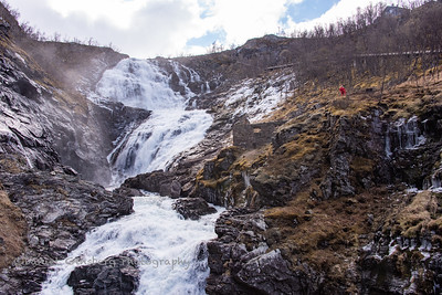 Waterfall with actress dressed as legendary Huldra at Flåm Railway train stop in Myrdal, Norway.