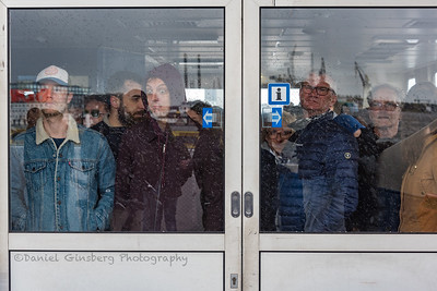 People standing behind glass door on ferry in Amsterdam.