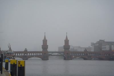 A bridge in the fog that crosses from East Berlin to West Berlin.