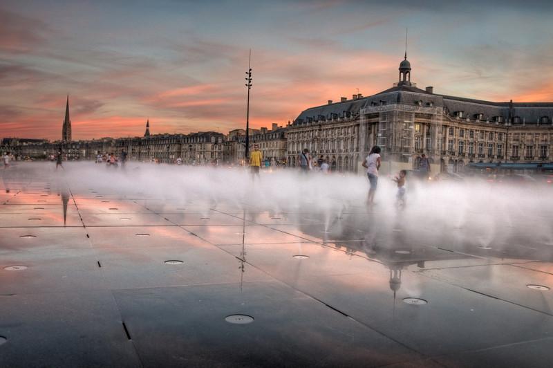 The sun is setting at the Miroir d´eau, in front of Place de la Bourse in Bordeaux, France.