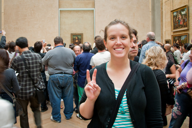 Sasha striking a peace sign in front of the Mona Lisa.